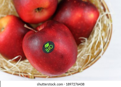 Red natural apple with bio sticker, apples harvest, agricultural raw fresh fruit in a basket on white background