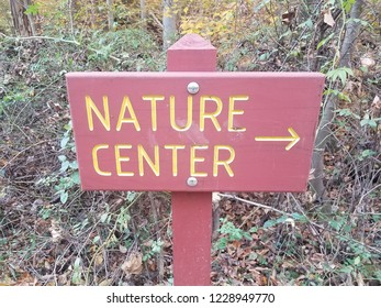red nature center sign with right yellow arrow