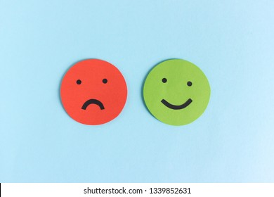 Red negative and green positive paper smileys composed on blue background