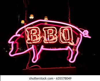 Red neon BBQ Pig sign on a black background in a restaurant window