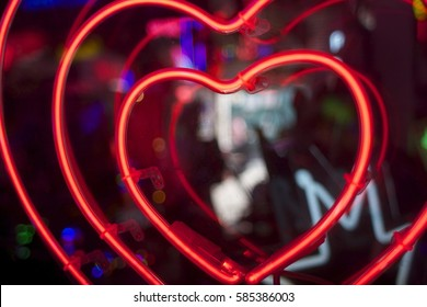 red neon concentric love hearts on clear perspex, narrow depth of field
