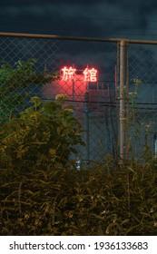 """Parole rouge néon en japonais signifiant """"Hôtel traditionnel"""" (Ryokan) derrière une clôture entourée de plantes et d'herbe la nuit dans les rues de Tokyo en été."""