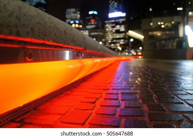 Red neon lights circulating underneath the stone seating reflecting on the stone pavement in Perth tourism hot spot Elizabeth Quay