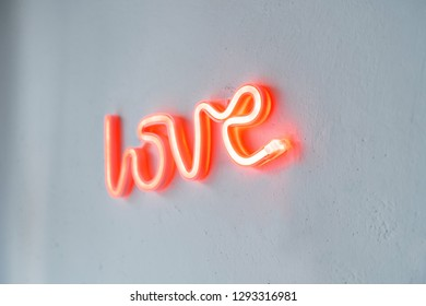 Red Neon Love Sign on a white wall. Close view with selective focus.