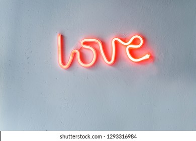 Red Neon Love Sign on a white wall. Horizontal view.