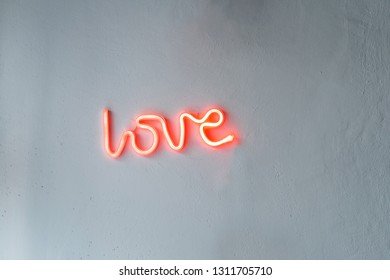 Red Neon Love Sign on a white wall.