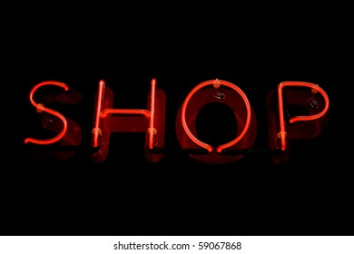 Red neon sign of the word 'Shop' on a black background.