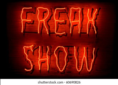 Red neon sign of the words 'Freak Show' on a black background.