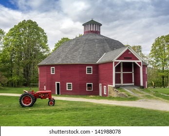 Red New England barn with vintage tractor in foreground