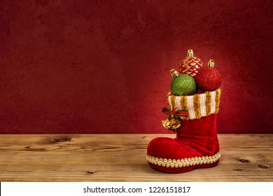Red Nicholas boot with three Christmas tree balls on a wooden board before a red wall