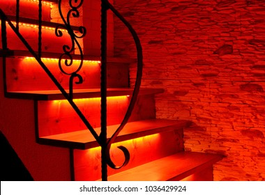 Red night LED lighting wooden stairs with antique railing