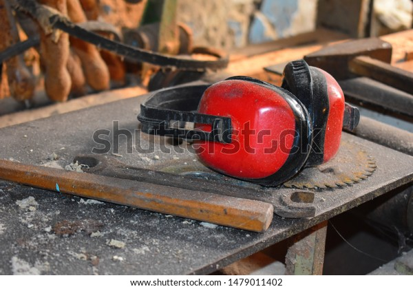Red noise-protective earphones of wood working carver. Carpenter's workshop with slips. Desktop of the joiner.