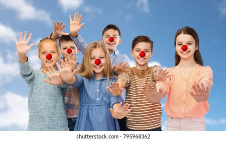 red nose day, charity and childhood concept - happy smiling children with clown noses waving hands over blue sky background