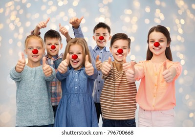 red nose day, charity and childhood concept - happy smiling children with clown noses showing thumbs up over festive lights background