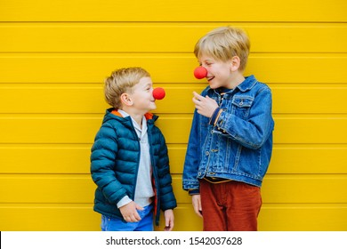 Red Nose Day Concept. Happy little brothers looks at each other wearing red clown noses having fun together on sunny autmn day outdoor, yellow background. Two kid playing together. Red Nose Day
