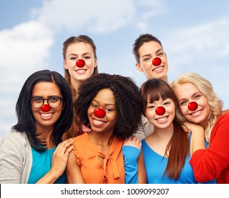 red nose day, diversity and people concept - international group of happy smiling different women with clown noses hugging over sky background