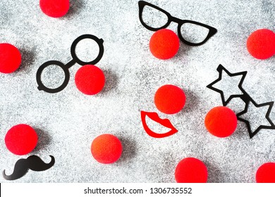Red Nose Day, red noses with glasses, moustache on grey background. Toned deep negative.