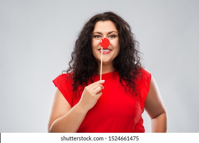 red nose day, party props and photo booth concept - happy woman with clown nose posing over grey background