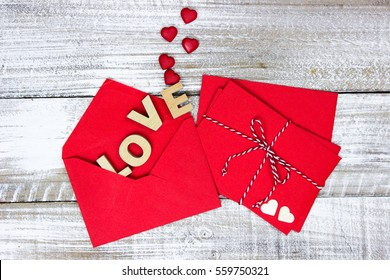 Red note cards and letter envelopes tied in string with wooden hearts and the word LOVE on whitewash rustic antique wood background; Valentines Day, Christmas and love concept with white copy space