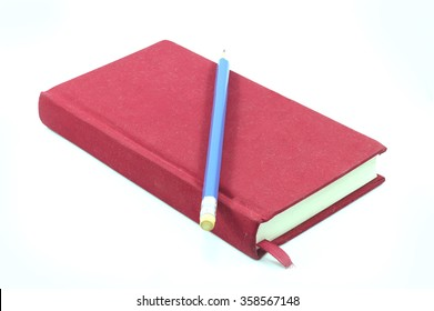 red notebook and blue pencil on white background
