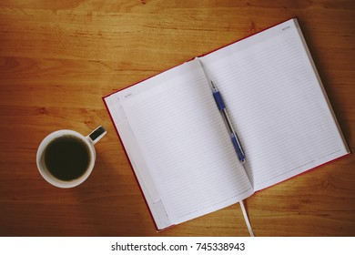 Red notebook and cup of coffee on a office desk