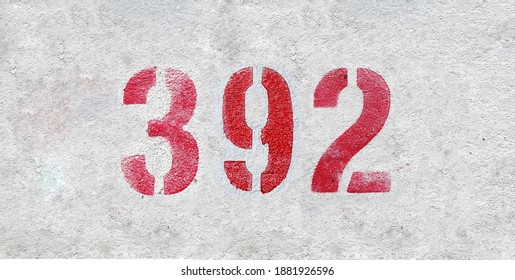 Red Number 392 on the white wall. Spray paint.