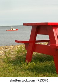 red ocean-side picnic table and red boat