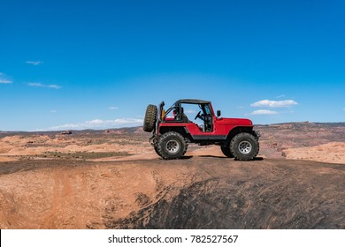 Red off road vehicle sits on top of slick rock in Moab Utah with blue sky in the background