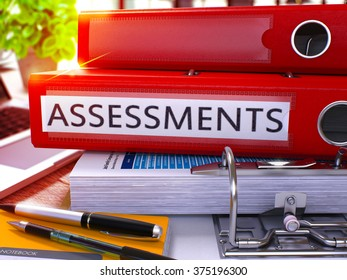 Red Office Folder with Inscription Assessments on Office Desktop with Office Supplies and Modern Laptop. Assessments Business Concept on Blurred Background. Assessments - Toned Image. 3D