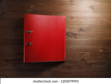Red office folder on wood table background. Blank file folder binder with copy space. Flat lay.
