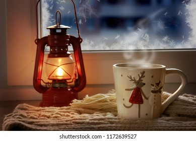 Red oil lamp and a new cup with a deer against the background of the evening window.