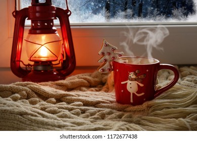 Red oil lamp and a new cup with a snowman against the background of the evening window.