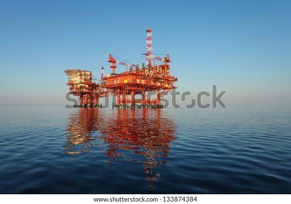 red oil rig platform on calm blue sea