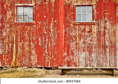 Red old barn with two windows and lonely bench, no sky and no horizon