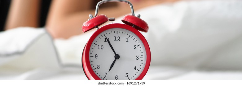 Red old fashioned alarm clock set at seven in morning while woman sleeping at background in her bed closeup