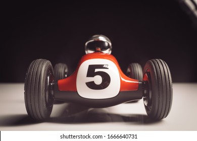 Red old racing car with number five painted on it