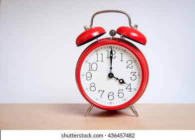 red old retro style alarm clock on wood table. Alarm clock shows four o`clock