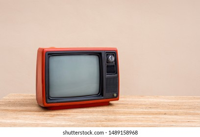 Red old television receiver on wood table with cement wall background. Retro, vintage old TV