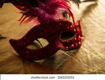 Red old vintage venecian mask with red  feathers on yellow wrap backgrund