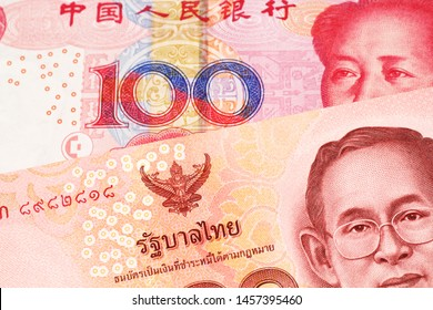 A red one hundred Thai baht along with a red one hundred yuan note from the People's Republic of China, close up in macro