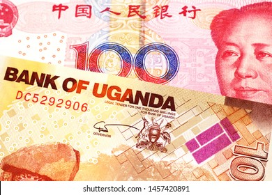 A red one hundred yuan bill from China with a one thousand Ugandan shilling bill close up in macro