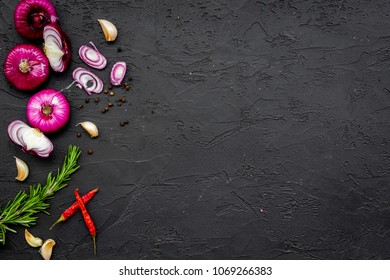 Red onion among spices rosemary, garlic, chili peper on black background top view space for text