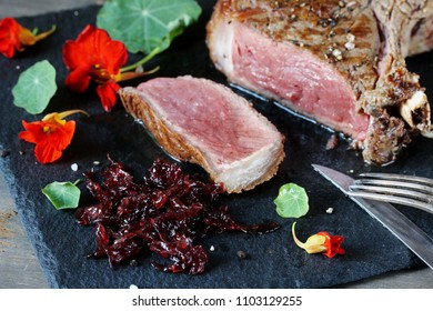red onion marmalade is served to the steak on a slate board. nasturtium as decoration and spicy greens