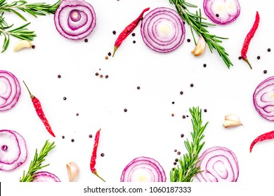 Red onion rings as seasoning. Onion near chili peper, rosemary, black peper, garlic on white background top view