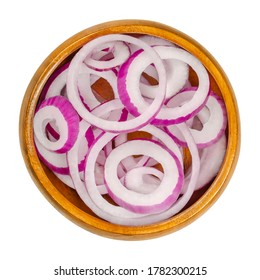 Red onion rings in wooden bowl. Slices of the onion cultivar Allium cepa with purplish red skin and white flesh tinged with red. Closeup, from above, on white background, isolated, macro food photo.