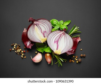 red onion and spices on black background, top view