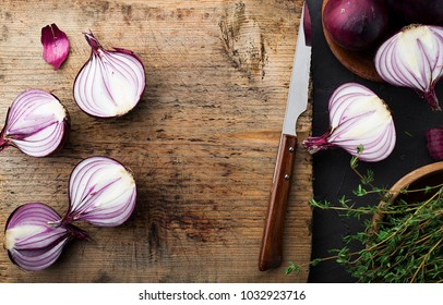 Red onions on an old vintage wooden cutting board with a knife and thyme. Top View