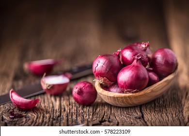 Red onions on very old oak wooden board.