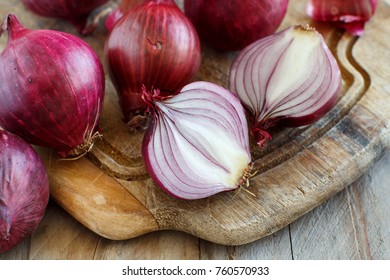 Red onions on a wooden board close up
