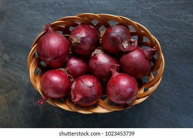 Red onions in wicker basket on slate table top